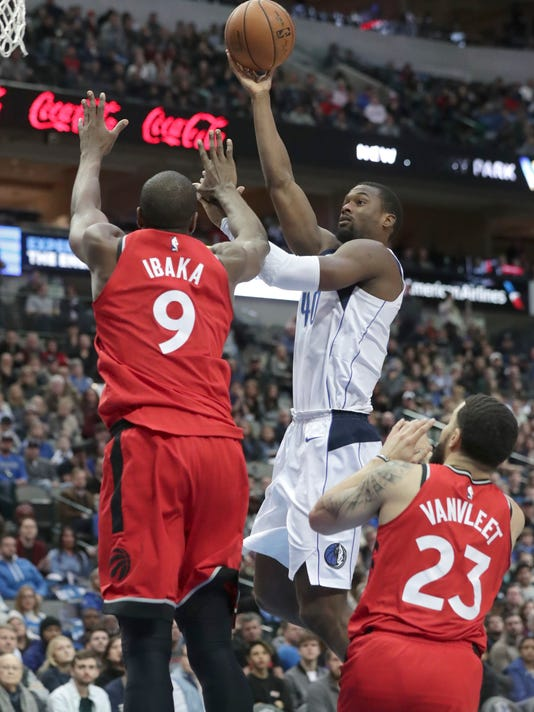 Dallas Mavericks center Salah Mejri (50) shoots against Toronto Raptors defenders Serge Ibaka (9) and Fred VanVleet (23) during the second half of an NBA basketball game in Dallas, Tuesday, Dec. 26, 2017. (AP Photo/LM Otero)