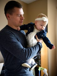 Rick Feuling holds his daughter Claire Friday, Oct.