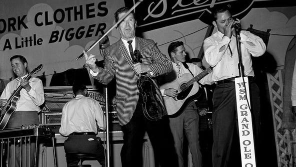 Roy Acuff, center, performs before a packed house during