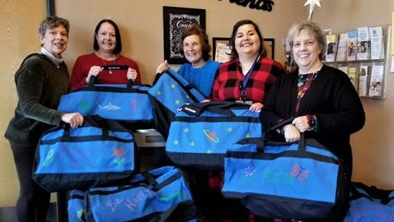 Members of Altrusa International of Salina club Kay Quinn, from left, Kristina Litchman, Mary Lou McKenzie, Michele Nightingale, and Linda Smith hold decorated duffel bags to give to children in foster care as part of their Kids on the Move project. The project won second place in its district.