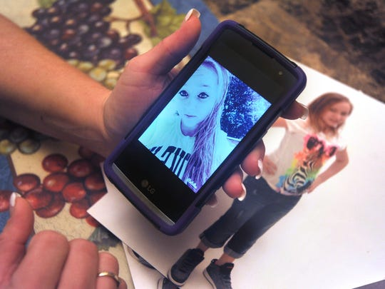 Kesha Frye looks at a photo of her daughter Alexis Baxter on on a cell phone. Alexis died unexpectedly at age 14 in the home of her interim guardians on Nov. 27.
