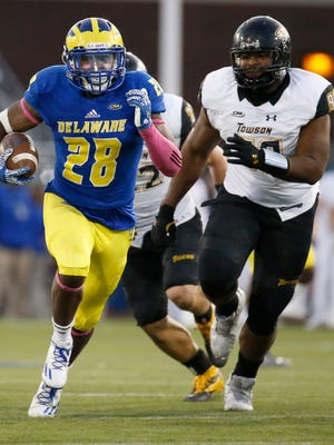 Delaware running back Thomas Jefferson (left) gets past Towson lineman Zain Harps Upshur on his 40-yard touchdown run to cap scoring in the fourth quarter of the Blue Hens' 20-6 win at Delaware Stadium Saturday.