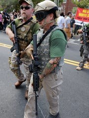 Two members of a private militia patrol the Charlottesville rally where white nationalists and counter-protesters clashed on Aug. 12, 2017.