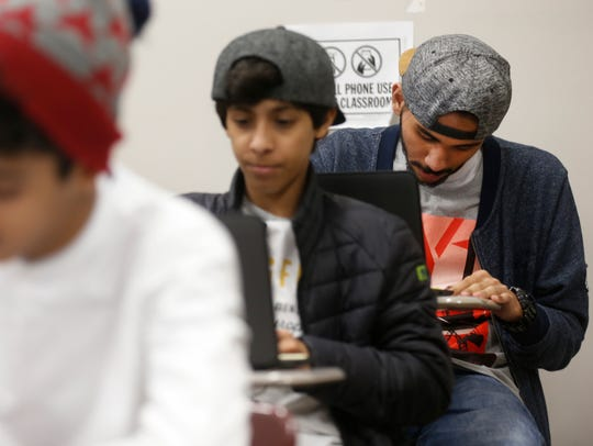 Ammar Bukhari, right, works on an assignment during