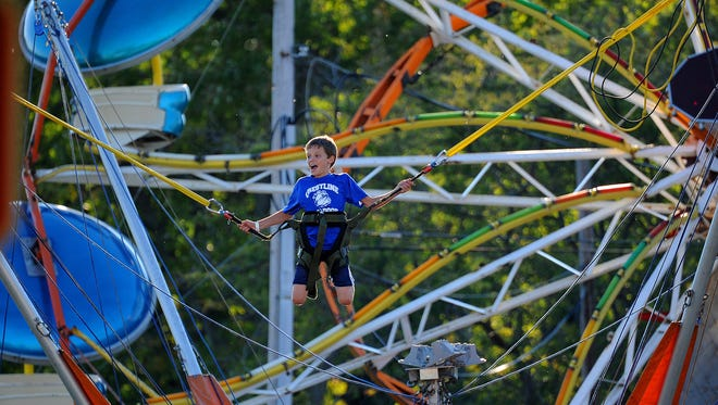 Blaine Barker, 12,  of Crestline enjoys the Euro Bungee attraction at the Harvest Festival in 2014.