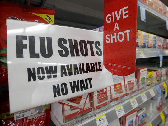 FILE - In this Sept. 16, 2014, file photo, a sign telling customers that they can get a flu shot in a Walgreen store is seen in Indianapolis. Kids may get more of a sting from flu vaccination this fall: Doctors are gearing up to give shots only, because U.S. health officials say the easy-to-use nasal spray version of the vaccine isn't working as well as a jab. Needle-phobic adults still have some less painful options. But FluMist, with its squirt into each nostril, was the only ouch-free alternative for children, and has accounted for about a third of pediatric flu vaccinations in recent years. (AP Photo/Darron Cummings, File)