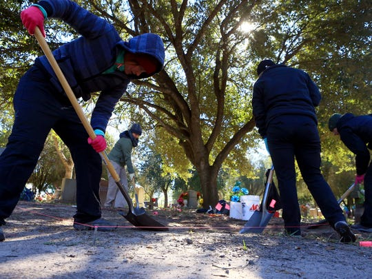 Graduate students from Texas State University remove dirt as they search for bodies of migrants that may be buried at the Sacred Heart Burial Park on Saturday, Jan. 7, 2017, in Falfurrias.