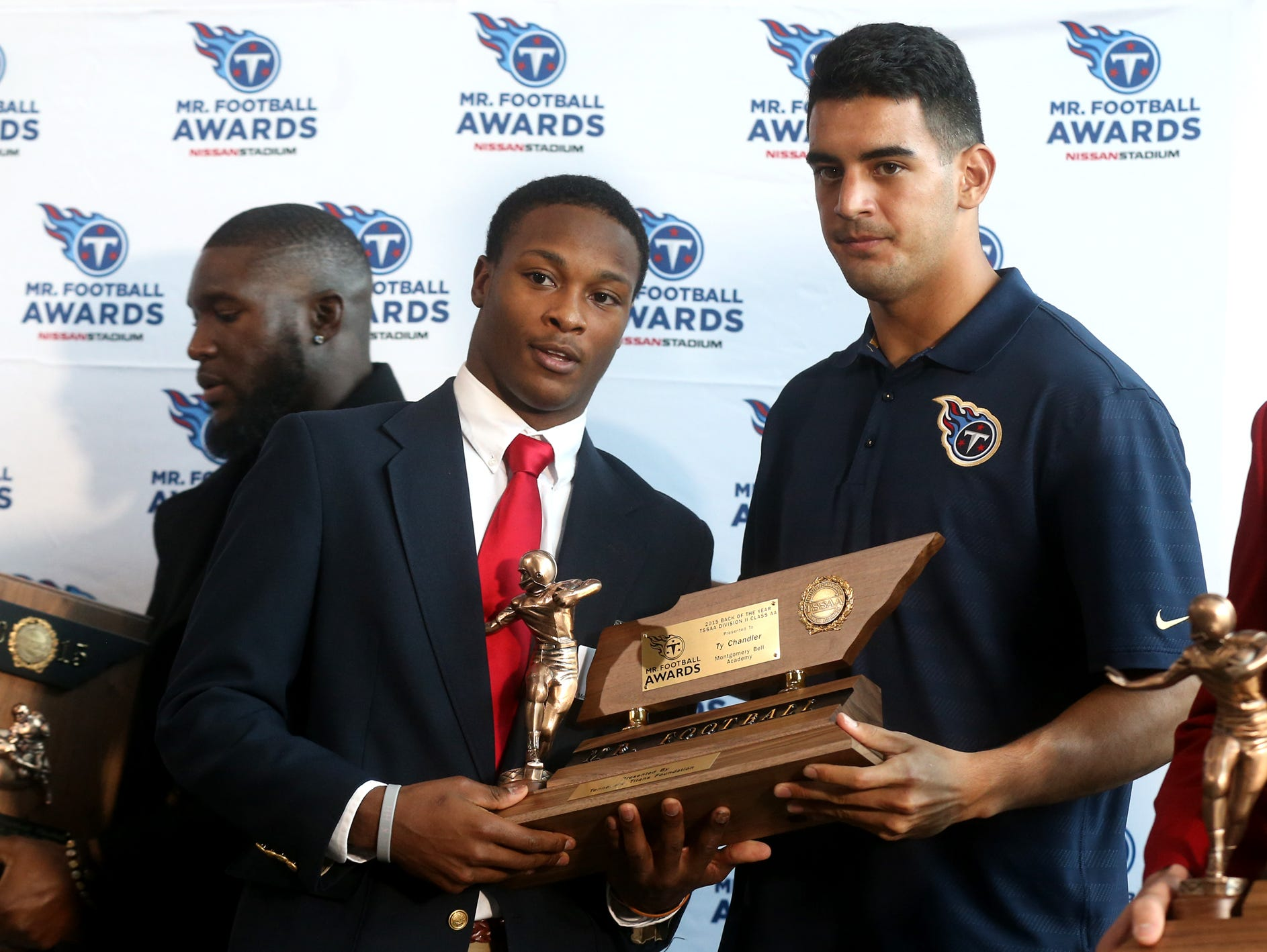 MBA's Ty Chandler, left, accepts the Mr. Football award for Division II-AA Back of the Year, from Tennessee Titans quarterback Marcus Mariota, Monday.