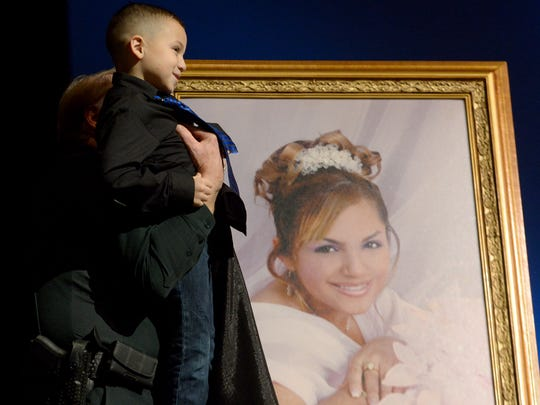 A portrait of fallen Madison County Deputy Rosemary Vela is unveiled by her son, Jayden, during the 2nd Annual Blue Strong event Thursday at the Carl Perkins Civic Center. This year's event was held in her memory.