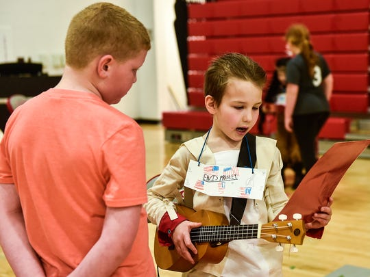 Dressed as Elvis and deep in his character first grader Zack Bowers reads Elvis' bio to another Elgin Elementary student on Friday during the Living Wax Museum event held by the school's first graders.