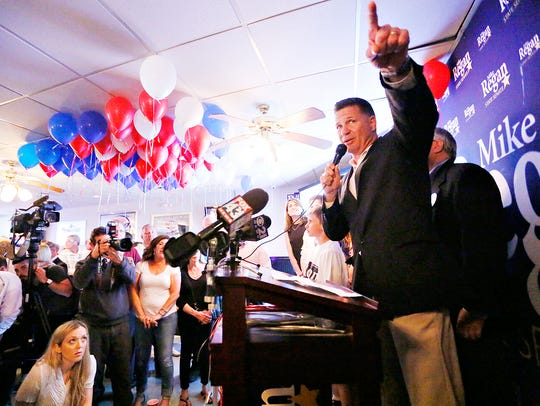 Mike Regan speaks during a watch party at Nick's 114