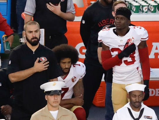 In this Sept. 1, 2016 file photo, former San Francisco 49ers quarterback Colin Kaepernick, center, sits during the national anthem before an NFL preseason football game against the San Diego Chargers in San Diego. As his career was winding down and while Barack Obama was in office, Kaepernick refused to stand when the anthem was played during NFL games, citing police brutality against black people and other forms of racial injustice.