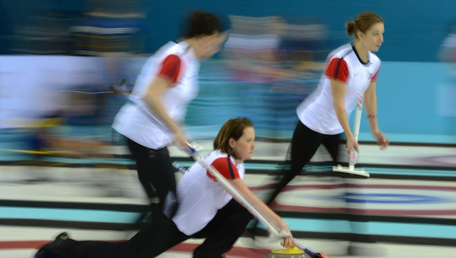 Ann Swisshelm, left, Debbie McCormick, center, and Jessica Schultz and the USA open with a 7-4 loss to Switzerland in curling.