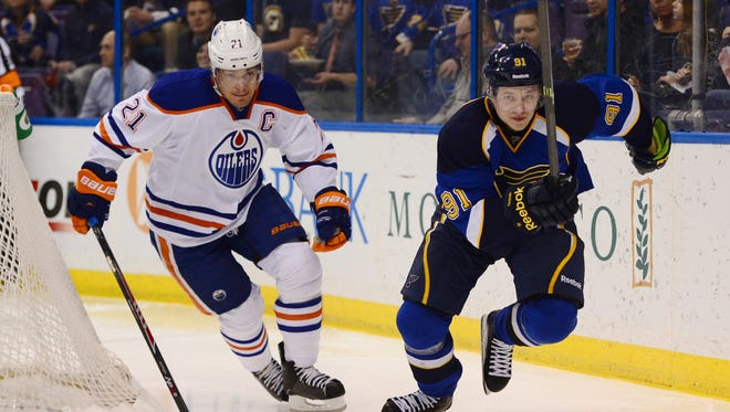 Edmonton Oilers defenseman Andrew Ference (21) and St. Louis Blues right wing Vladimir Tarasenko (91) chase a loose puck during the second period at Scottrade Center.