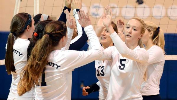 Holy Trinity players exchange high fives after defeating West Shore 3-1 in Saturday's FHSAA volleyball regional semifinals.