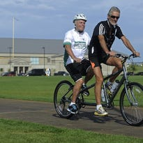 Harald Vik, the blind-deaf Norwegian bicyclist, signs with Robert Skarsbakk as they talk with Jennifer Weber-Fetzer at the Sanford Fieldhouse in Sioux Falls, SD; Friday, Sept. 4, 2015. They biked with the SanfordÕs orthopedics team who helped him last year after being hit by a car in Sioux Falls.