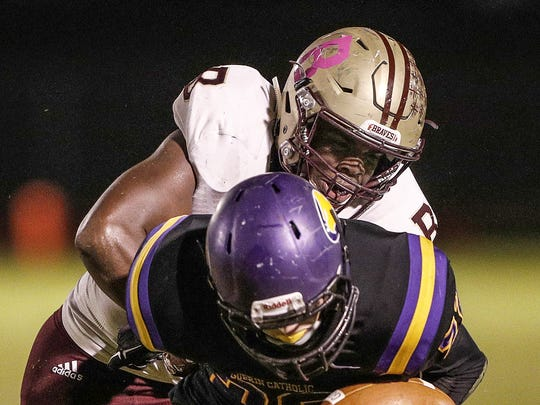 Brebeuf Jesuit's Jay Higgins (44) forces a fumble by knocking the ball out of the hands of Guerin Catholic running back Thomas Kaser (22), Oct 20, 2017.