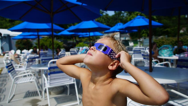 Seven-year-old Chase Harden checks for the beginning of the Eclipse at Westminster swim club on Monday afternoon.