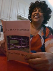 Robena Egemonye looks Wednesday morning at her latest book in her Anderson home.