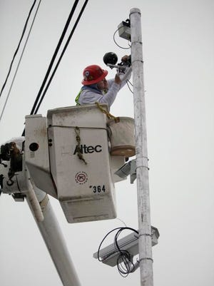 A worker for O'Connell Electric installs a red light camera near the intersection of Norton and Clinton Streets.
