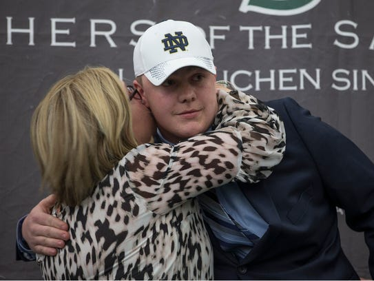 John Olmstead gets a congratulatory hug from his mother