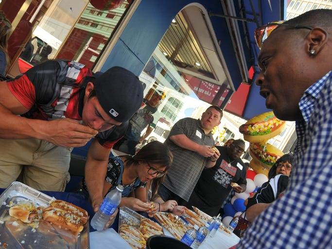 Former Detroit Pistons player Rick Mahorn, right, coaches a contestant during at 4th annual American Coney Island Coney Dog Eating contest in downtown Detroit, Thursday, Aug. 28. About 30 contestants scarfed down Detroit's favorite dogs to raise money for the charities of the city's police and fire departments.