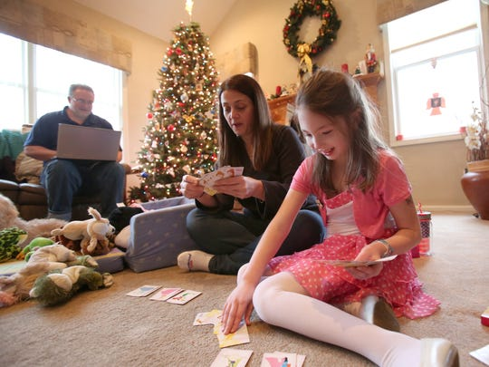 Amanda Houser, 10, with her parents Dean and Maryanne at their Suffern home on Dec. 23. The family wants New York to finally launch a medical marijuana program, which they hope will control Amanda's seizures.