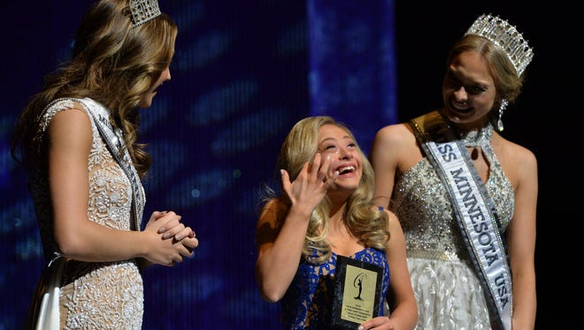 """Mikayla Holmgren, center, accepts the """"Spirit Award"""" during the 2018 Miss Minnesota USA contest in Burnsville, Minn. on Sunday, Nov. 26, 2017. Presenting the award are Tori Triffin, Miss Minnesota Teen 2017, left, and Meridith Gould, Miss Minnesota USA 2017. Holmgren, 22, made history Sunday night when she became the first woman with Down syndrome to compete in the Miss Minnesota USA pageant. Holmgren, who also is believed to be the first woman with Down syndrome to compete nationwide, was named the recipient of the Miss Minnesota USA Spirit Award and Director's Award."""