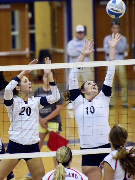 Chambersburg's Caitlin Vrabel (20) and teammate Jess Howe (10) battle at the net against Red Land during volleyball action last fall. All Trojan teams will now be able to take advantage of strength and conditioning training by Results Fitness.