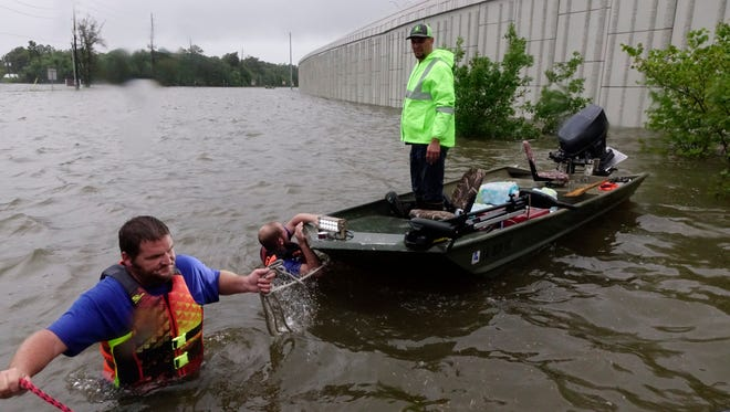 Shannon Breaux pulls a boat through shallow water as Brett Lejeune looks on as they help Hurricane Harvey flood victims in Houston.