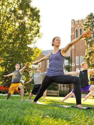 Lynne Staropoli Boucher leads a yoga class on the front lawn of Smyth Hall at Nazareth College.