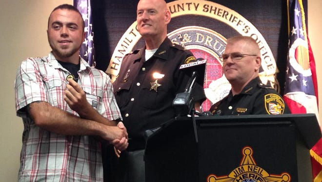 Hamilton County Sheriff Jim Neil (center) thanks Sam Haynes, of Amelia, who stopped a woman swerving and driving erratically on I-275 on Friday. Police said the driver later admitted to taken heroin and meth. Haynes' video of the incident has gone viral.