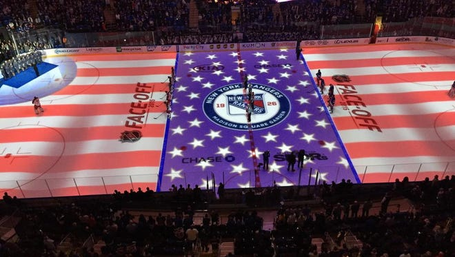 The Madison Square Garden ice is adorned with the American flag at last season's home opener.