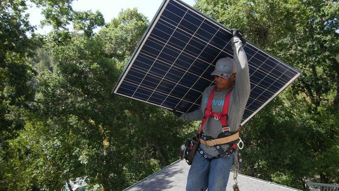 A worker installs a Sunrun Inc. solar panel on a house. California-based Sunrun is expanding to Wisconsin.
