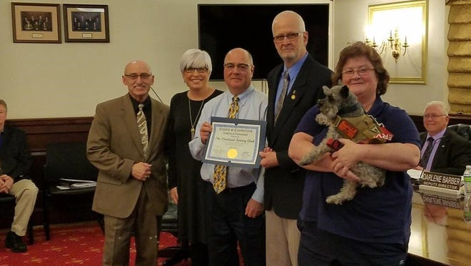 The Cumberland County Freeholder Board recognized the Vineland Rotary Club at its Feb. 27 meeting for the club's support and coordination of the Wreaths of Remembrance Ceremony on Dec. 16, 2017, at the Cumberland County Veterans Cemetery. (From left) Joe Derella, Cumberland County Freeholder Director; Sue Sauro, member, Vineland Rotary Club; David Schad, treasurer, Vineland Rotary Charities Foundation; Ken Dondero, president, Vineland Rotary Club; and Diana Pitman, Cumberland County Director of Veterans Affairs, with Gunnar; are pictured at the meeting.