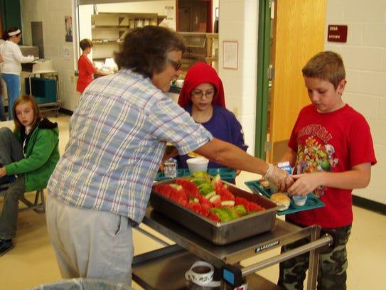 A representative from the Farm to School program serves