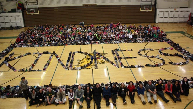 Students and staff of the Edgar School gathered in the Edgar High School with the shoes they collected for donation.