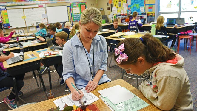 University of South Dakota student teacher Ellie Hart, who is teaching in Julie Sehr's third-grade class at Harvey Dunn Elementary School, works with Katherine Cardona, a third-grader, on a reading exercise Wednesday, Oct. 5, 2016, in Sioux Falls.