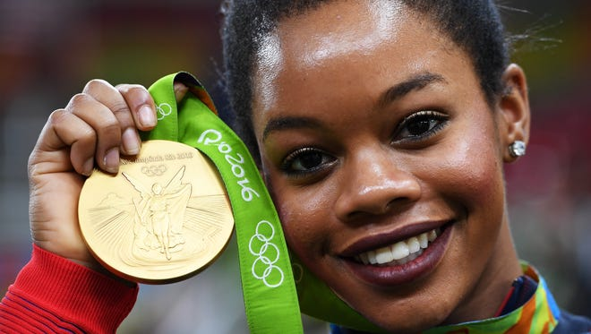 Gabrielle Douglas of the United States poses for photographs with her gold medal after the medal ceremony for the Artistic Gymnastics Women's Team on Day 4 of the Rio 2016 Olympic Games at the Rio Olympic Arena on August 9, 2016 in Rio de Janeiro, Brazil.