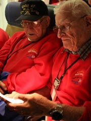 World War II veterans Dave Bergan and Dave Teich peruse their thank-you letters on the plane ride home for Honor Flight Northern Colorado in 2010.