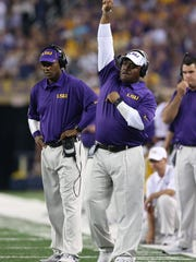 LSU Tigers defensive backs coach Corey Raymond (left)