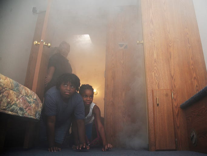 Mikiyah Hardy and Teri Booker crawl through the Pike Road Fire Safty House during Montgomery County National Night Out at Pike Road own Hall on Tuesday, August 4, 2014, in Pike Road, AL.