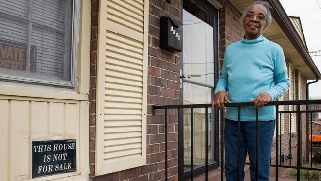 """Sallie Dowell stands on her porch at her Southside Avenue house. She has put a sign on her house reading """"This house is not for sale"""" to keep real estate investors off her property."""