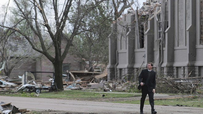 The Rev. David Otten, from Immanuel Lutheran Church in Dimock walks past Zion Lutheran Church in Delmont in May 2015 after the church was destroyed by a tornado.  a tornado.