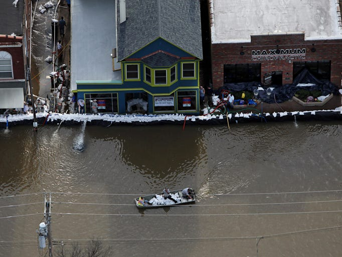 A boat carrying sandbags moves down South Central Avenue