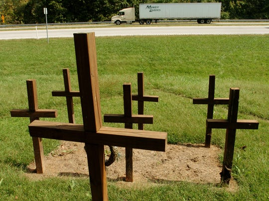Seven wooden crosses mark the spot where seven people