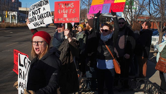 Protesters, including Amanda Bremmon, from left, Kelly Sullivan and Alisha Grove, all of Sioux Falls, take part in the Hold Them Accountable: Legislative Coffee Protest Saturday, Feb. 20, 2016, in front of the downtown Holiday Inn in Sioux Falls.