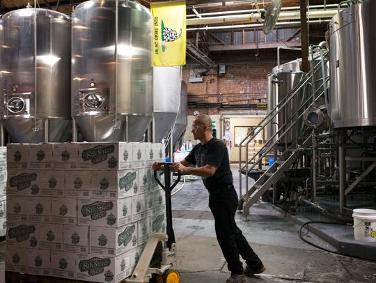 Javier Felix moves a pallet of 8th Street Ale into