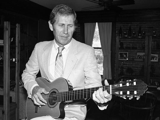 Chet Atkins tries out the seventh of his new guitars