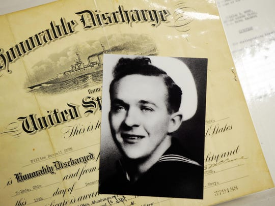A picture of William Dunn during his service in the U.S. Navy during World War II. Behind the picture is his honorable discharge from December 1945.